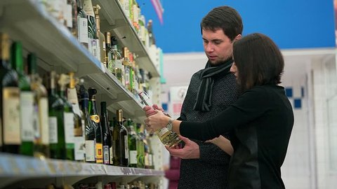 The young couple husband and wife chooses wine in a grocery store to go to visit friends.