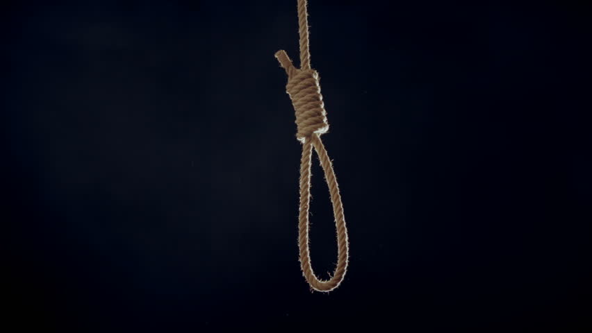 Hangmans noose falling into frame hard lit from behind