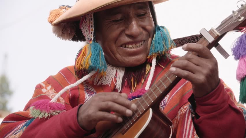 Native quechua man using a colorful handcrafted chullo and a highlander hat, singing with his guitar on the alleys of Cusco | Shutterstock HD Video #24242390