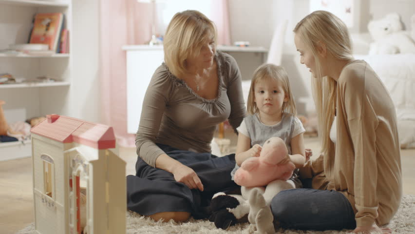 Grandmother, Mother and Her Little Cute Daughter have a Big Hug. They're in a Children's Room which is Pink and full of Toys. Shot on RED EPIC-W 8K Helium Cinema Camera.