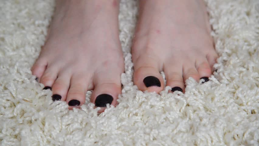 Womens feet are on beige carpet #24260030