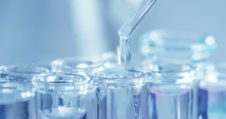 In a laboratory, a scientist with a pipette analyzes a colored liquid to extract the DNA and molecules in the test tubes. Concept: research, biochemistry, nature, pharmaceutical medicine