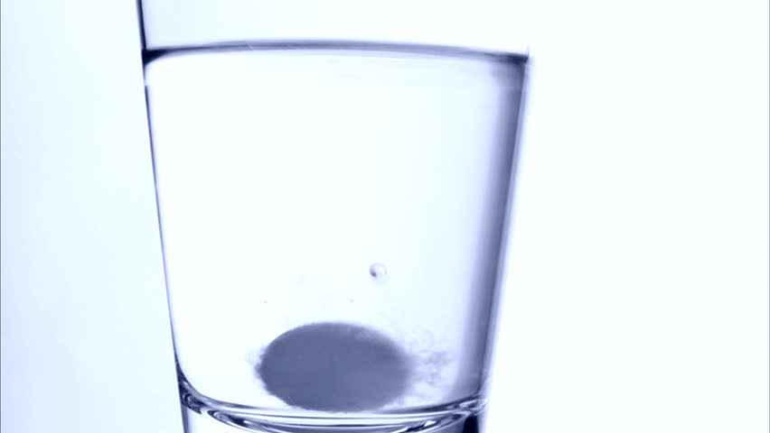 An effervescent tablet and a glass of water, close-up. | Shutterstock HD Video #2428520