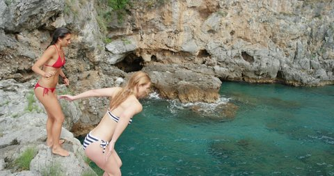 Athletic women jumping from cliff into sea best friends enjoying European summer holiday travel vacation adventure in Amalfi Coast Italy