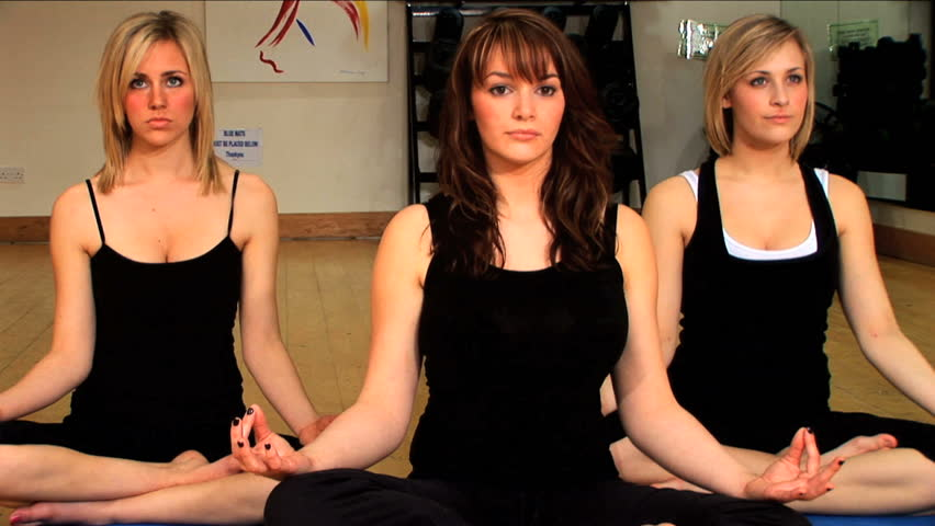 Beautiful girls perform yoga exercises at the gym