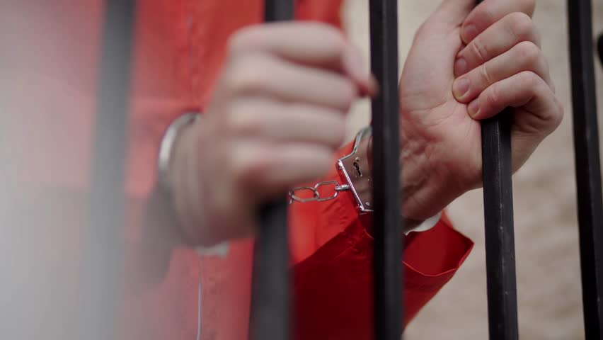 Male prisoner, adult, white waiting outside. Wearing handcuffs and an orange jumpsuit. Young offender, late twenties/ early thirties. Serving time/ awaiting trial in county jail. Convict in prison.