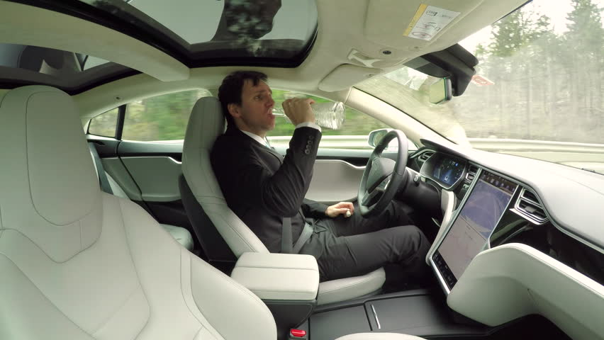 CLOSE UP: Irresponsible young businessman drinking alcohol behind the wheel while traveling in autonomous self-driving autopilot luxury electric driverless car. Male driver sipping vodka while driving #24320450