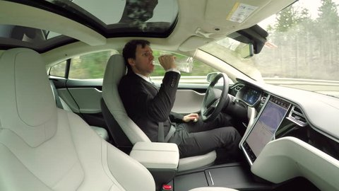 CLOSE UP: Irresponsible young businessman drinking alcohol behind the wheel while traveling in autonomous self-driving autopilot luxury electric driverless car. Male driver sipping vodka while driving