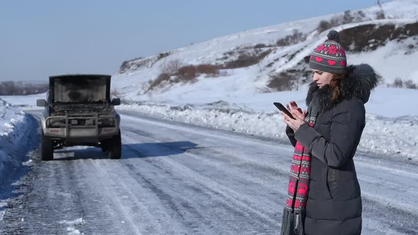 Broken car on a winter road and a woman wants to make a phone call to ask for help, but there is no connection, and she was crying | Shutterstock HD Video #24339680