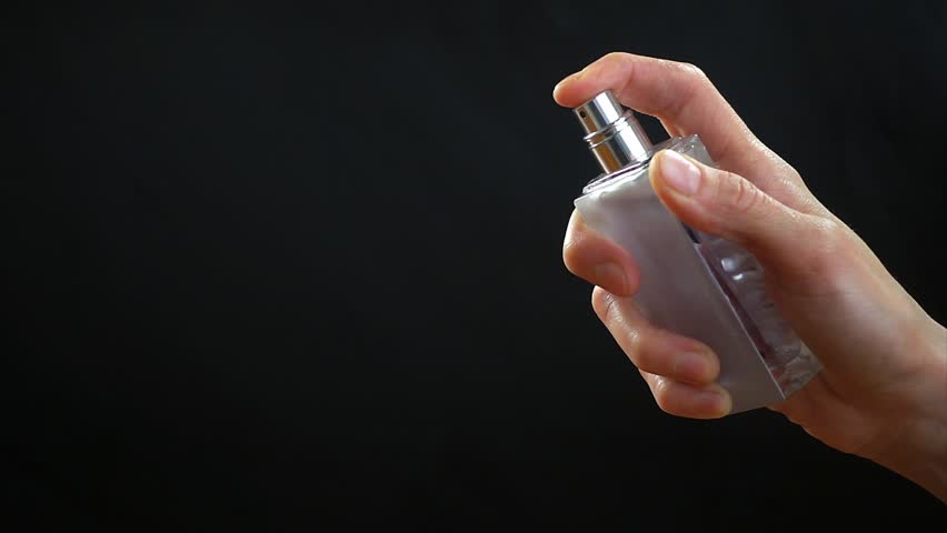 Woman's hand sprays perfume on black background, slow motion hd video