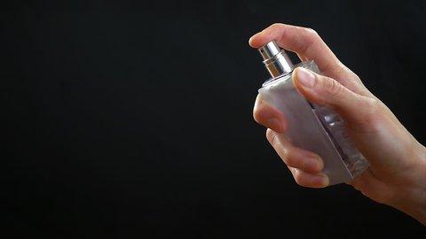 Woman's hand sprays perfume on black background, slow motion hd video