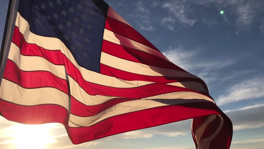 American flag flying in the wind at sunrise slow motion