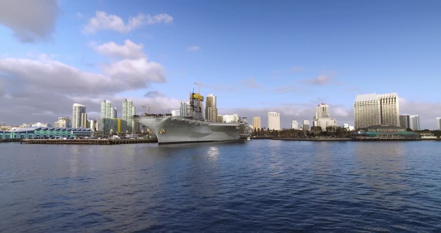 A wide, dramatic daytime establishing shot of the San Diego city skyline as seen from the bay. The USS Midway aircraft carrier is in the foreground. Part 2 of 2.