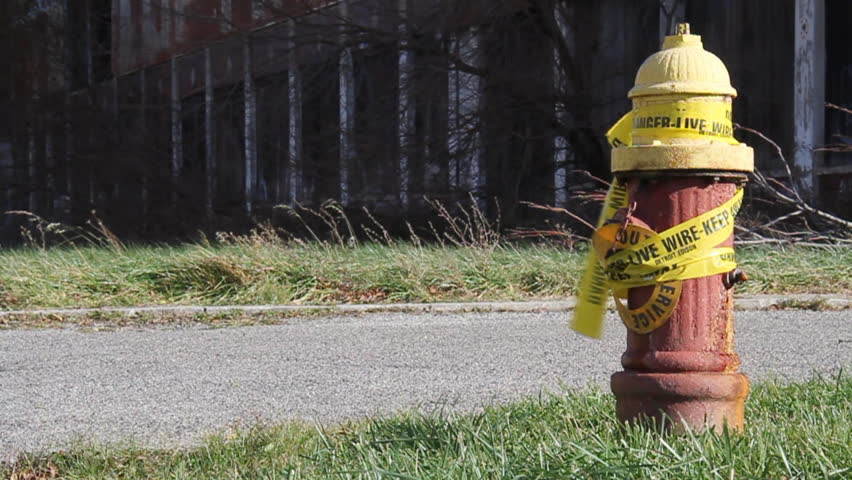 Urban blight in Detroit, Michigan. An old fire hydrant wrapped in caution tape near a decaying, abandoned factory.