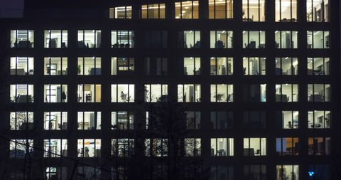 Office building in metropolitan area in late evening. People working 24 hours. Time lapse shot