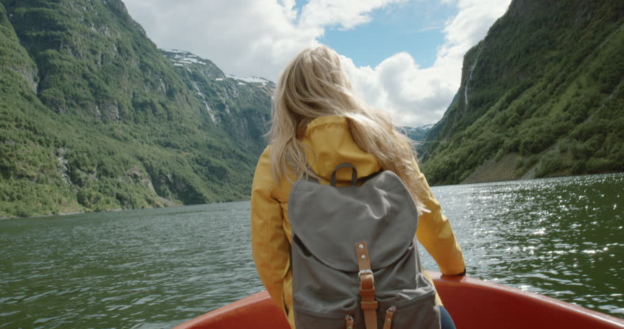 Woman sitting in boat on Fjord Norway hair blowing in wind traveling towards scenic landscape nature background view enjoying vacation travel adventure | Shutterstock HD Video #24369680