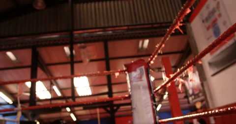 Pair of boxing gloves hanging on boxing ring in fitness studio