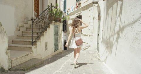 Young Tourist woman exploring European town Beautiful girl walking through street travelling enjoying summer vacation travel adventure Amalfi Italy