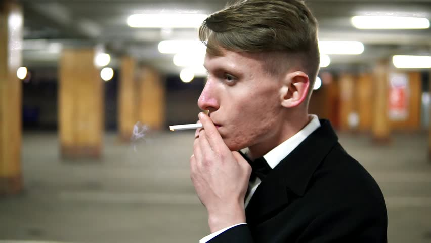 Closeup view of young blonde man in a black suit with a bow-tie smoking a cigarette in the parking. Waiting for someone. | Shutterstock HD Video #24372206