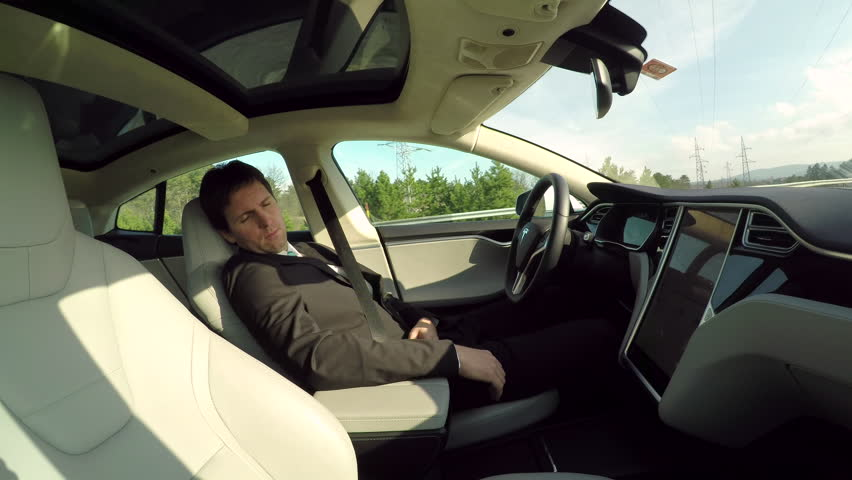 GRAZ, AUSTRIA - FEBRUARY 2nd 2017: Businessman sleeping behind self-driving steering wheel in autonomous autopilot driverless electric Tesla car. Deeply asleep man driving along the countryside road