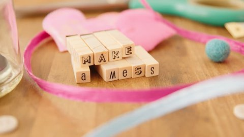 "Moving right to left along a table strewn with pretty coloured craft supplies and coming to rest on the words ""Make A Mess"" spelled out with wooden blocks."