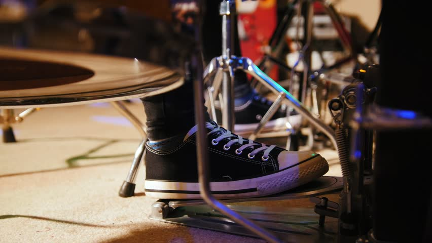 Drummer's foot in sneakers moving drum bass pedal