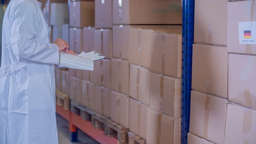 A pharmaceutical factory worker is putting stickers of different countries on boxes in the storage.