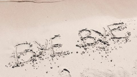 Bye bye writing on the sand being deleted by waves. Water washing away a writing on the beach