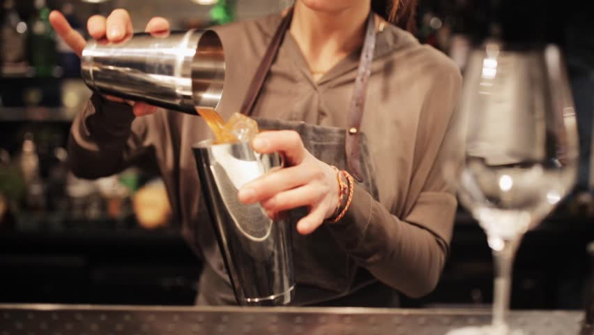 alcohol drinks, people and luxury concept - barmaid with shaker preparing cocktail at bar