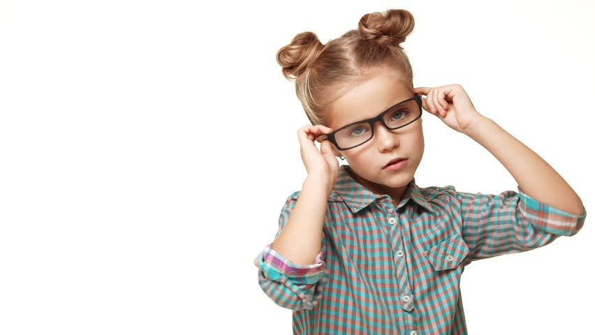 Small girl kid in plaid shirt and hair buns wearing glasses posing making faces on white background in slowmotion