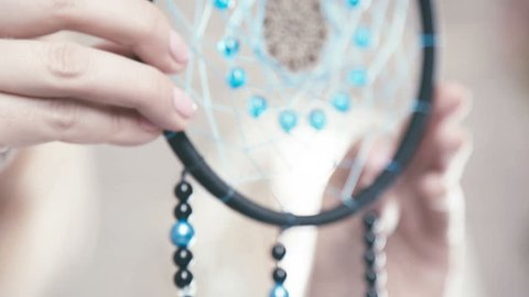 Close-up of female hands doing Dreamcatcher of black thread, turquoise beads and feathers. Dreamcatcher - design element bedrooms, Indians amulet, ward off evil spirits.