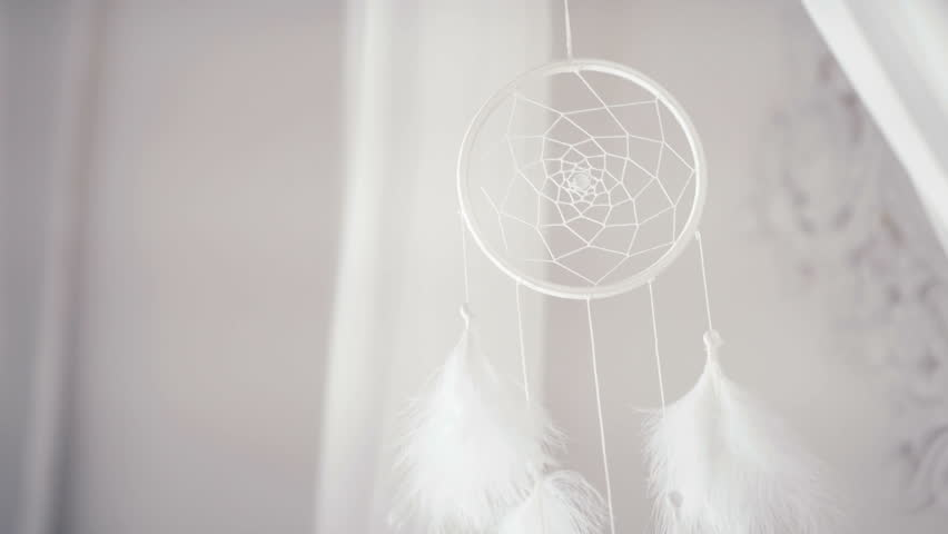 White Dreamcatcher hangs over the bed with a canopy and rotate slowly. Dreamcatcher - bedroom decor element, Indian amulets and charms against evil spirits. Homemade Dreamcatcher above the bed.