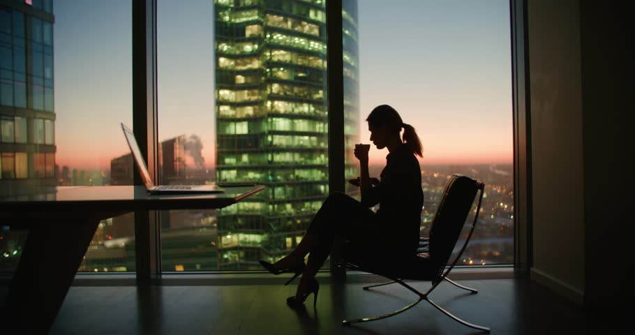 young woman businessman ceo sitting in a chair with a cup of coffee in the hands of the panoramic window in the office skyscrapers at sunset