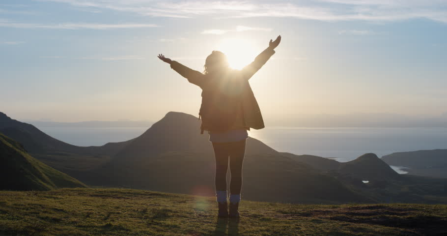 Woman with arms raised on top of mountain looking at Sunset view Hiker Girl lifting arm up celebrating life scenic nature landscape enjoying vacation travel adventure Isle of Skye Scotland