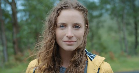 Close up portrait of Young Woman Smiling in nature with wet hair standing in rain Hiker Girl trekking cold stormy weather in Scotland Slow Motion