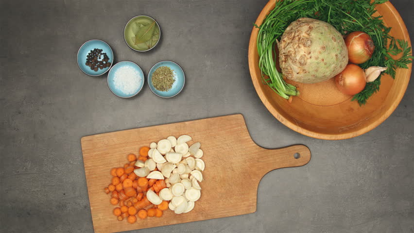 Top view on grey kitchen counter with ingredients and accessories for vegetable broth. Food stop motion animation.
