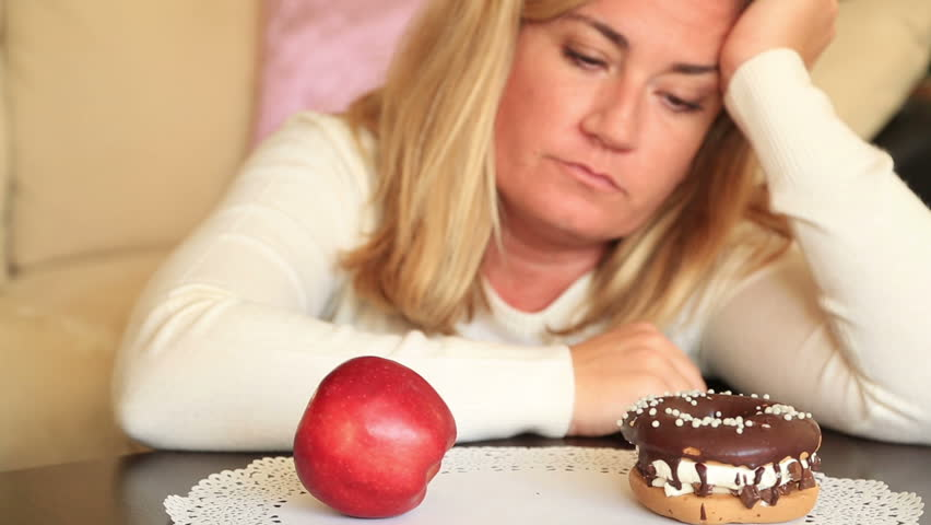 Woman choosing between Fruits and Sweets. Diet nutrition concept | Shutterstock HD Video #24431870
