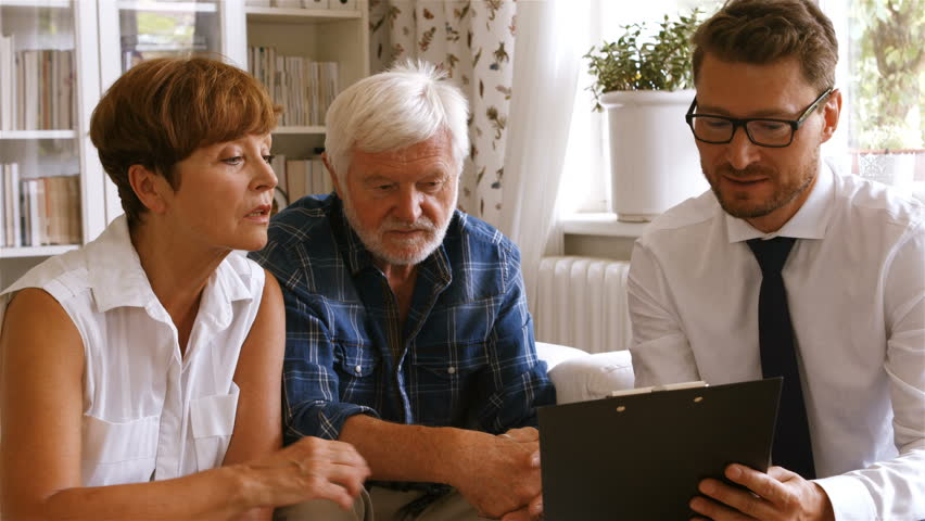 Front-view of Caucasian senior couple planning their investments with financial adviser at home
