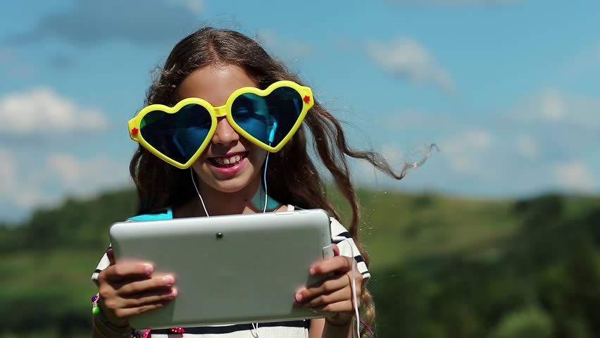 Attractive girl talks via tablet computer. Merry girl in big sunglasses in the shape of hearts communicates via tablet pc. Female in glasses with white tablet pc. Girl communicates through skype