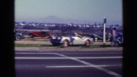 SAN DIEGO 1952: various people and beautiful cars parked on side of busy road with traffic