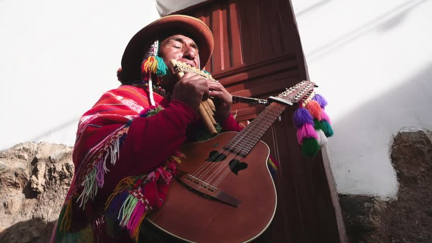 Native quechua man using a colorful handcrafted chullo and a highlander hat, singing with his guitar and quena on the alleys of Cusco | Shutterstock HD Video #24476030
