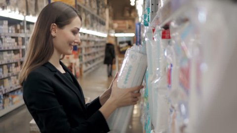 woman buys diapers at the supermarket, young mom mother shopping