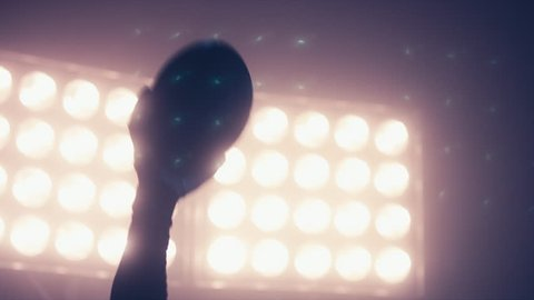 CU Silhouette of male American football player rising a ball in his hand against bright stadium illumination lights