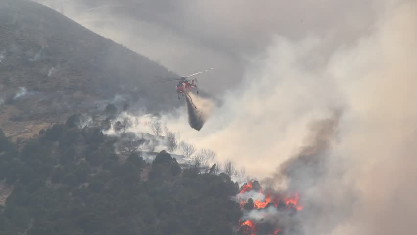 A helicopter battles a gigantic wildfire on a dry mountainside, dropping hundreds of gallons of water on the flames. | Shutterstock HD Video #2450504