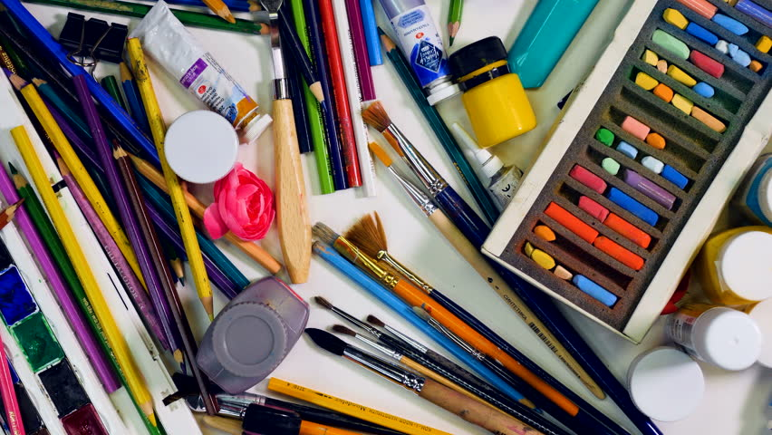 Chaos, mess on artists desk view from above. Artist, designer clear the table.