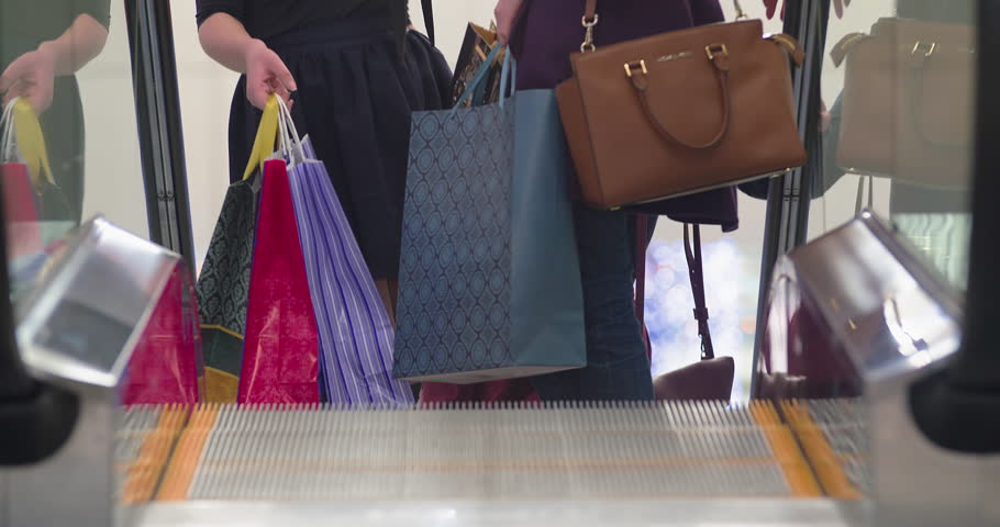Happy women friends shopping at the mall 4K video. Girls with sale boxes talk on escalator. View of female legs step on moving stairs.