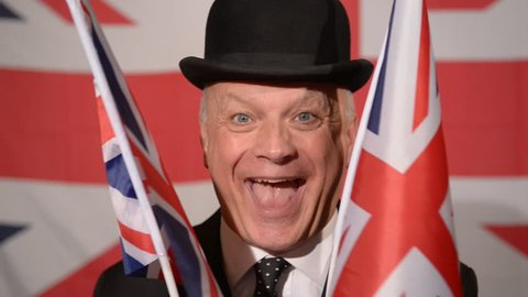 Very happy British businessman wearing traditional black bowler hat and suit, hiding behind two small Union Jack flags, the man reveals himself then the flags close again.