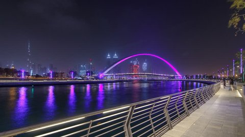 Illuminated Pedestrian Bridge over the Dubai Water Canal night timelapse hyperlapse along the promenade Skyscrapers skyline. It links Dubai Creek to Jumeirah Beach weaving through Deira, Downtown