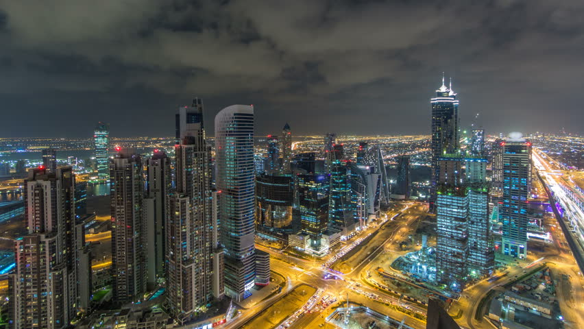 Dubai business bay towers illuminated at night timelapse. Traffic on road with intersection. Rooftop view of some skyscrapers and new towers under construction. #24564560
