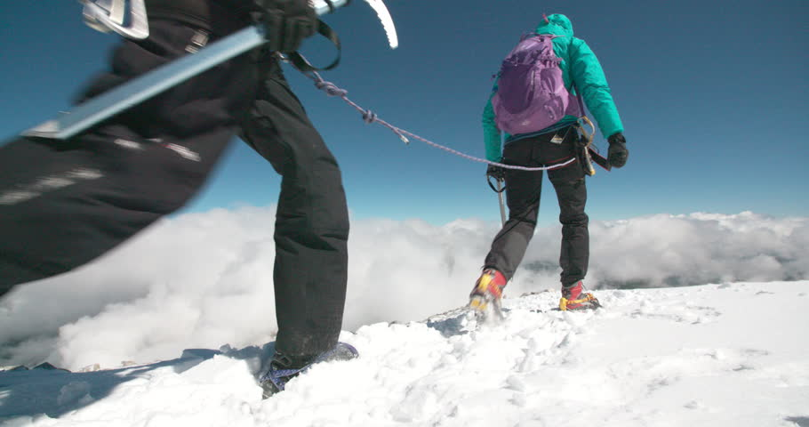 Two mountaineers descending a high alpine mountain to the waiting clouds and valley below.